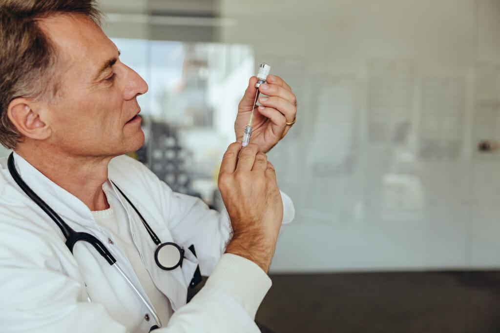 Ein Doktor mit einer Impfspritze