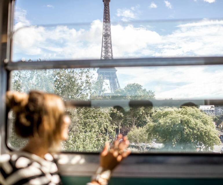 Frau in Bahn blickt auf Eifelturm