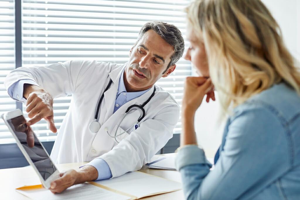 Ein Arzt zeigt seiner Patientin Therapiemöglichkeiten.