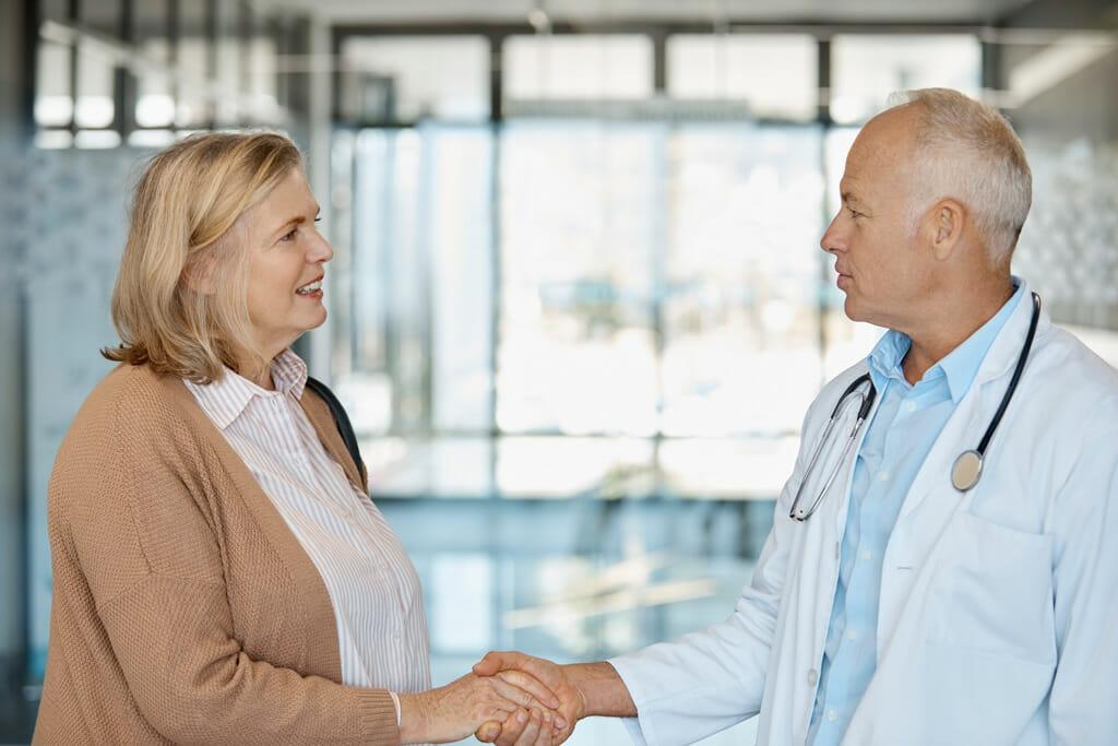 Eine Patientein und ihr Arzt reichen sich die Hand