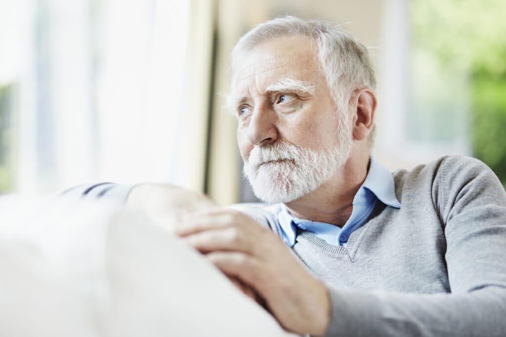 Ein älterer Mann blickt aus dem Fenster
