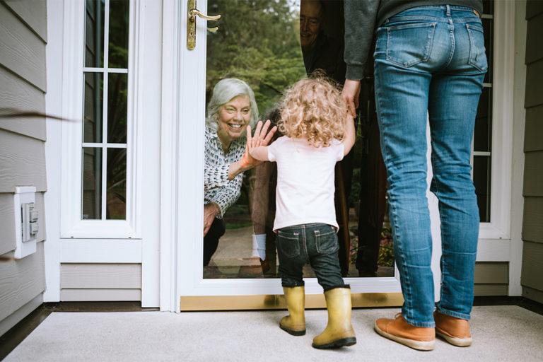 Seniorin begrüßt Enkel durch die Scheibe.