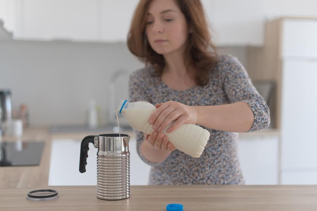 Eine Frau füllt Milch mit zwei Händen um