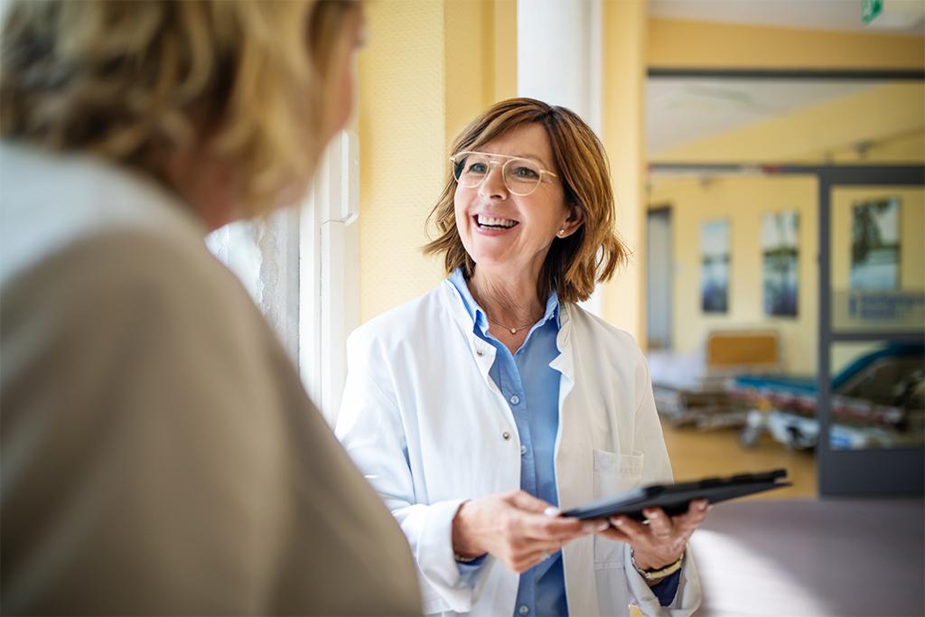 Laechelnde Aerztin spricht mit Frau im Krankenhaus